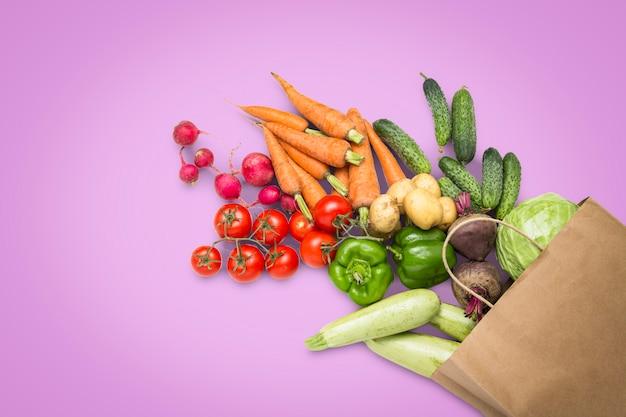 紙の買い物袋と明るいピンクの背景に新鮮な有機野菜。農場野菜の購入、健康管理、菜食主義の概念。カントリースタイル、ファームフェア。フラット横たわっていた、トップビュー