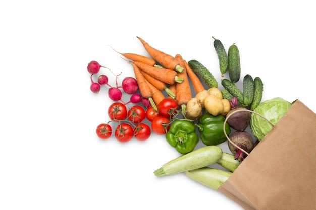 紙の買い物袋と白い背景の上の新鮮な有機野菜。農場野菜の購入、健康管理、菜食主義の概念。カントリースタイル、ファームフェア。フラット横たわっていた、トップビュー