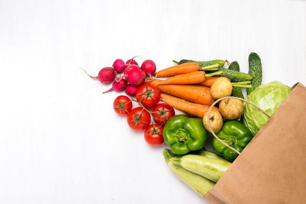紙の買い物袋と白い木製の表面に新鮮な有機野菜。農場野菜の購入、健康管理、菜食主義の概念。カントリースタイル、ファームフェア。フラット横たわっていた、トップビュー