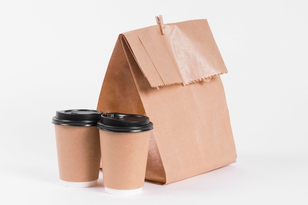 Paper shopping bag and coffee to go cups front view