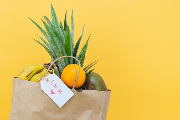 열대 과일로 가득 찬 종이 쇼핑백과 노란색 배경에 local이라는 라벨이 붙어 있습니다. 공간을 복사합니다.