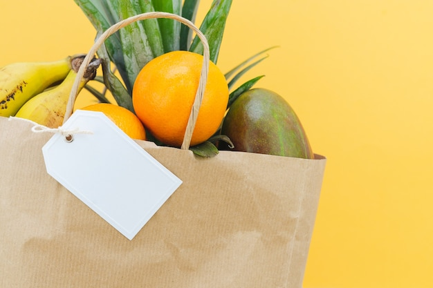 노란색 배경에 열대 과일과 흰색 라벨로 가득 찬 종이 쇼핑백. 모형. 공간을 복사합니다.