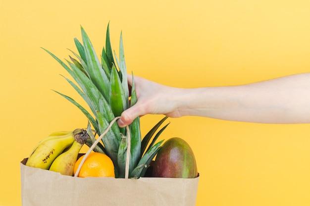 노란색 배경에 여성의 손이 있는 열대 과일로 가득 찬 종이 쇼핑백. 공간을 복사합니다.
