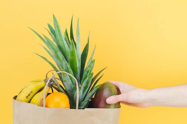 Paper shopping bag filled with tropical fruit with woman's hand on yellow background. copy space.