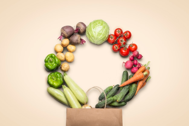 Paper shopping bag and fresh organic vegetables on a light background. concept of buying farm vegetables, care of health. circle shape. country style, farm fair. flat lay, top view
