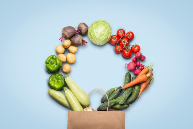 Paper shopping bag and fresh organic vegetables on a light blue background. concept of buying farm vegetables, care of health. circle shape. country style, farm fair. flat lay, top view