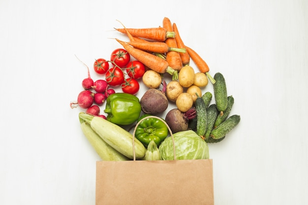 Paper shopping bag and fresh organic vegetables on a white wooden surface. concept of buying farm vegetables, taking care of health, vegetarianism. country style, farm fair. flat lay, top view