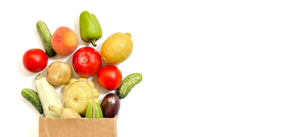 A paper shopping bag from which vegetables and fruits fall out namely tomato cucumber squash pepp