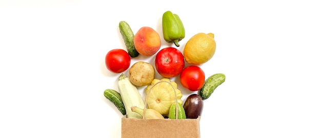 A paper shopping bag from which vegetables and fruits fall out namely tomato cucumber squash pepper