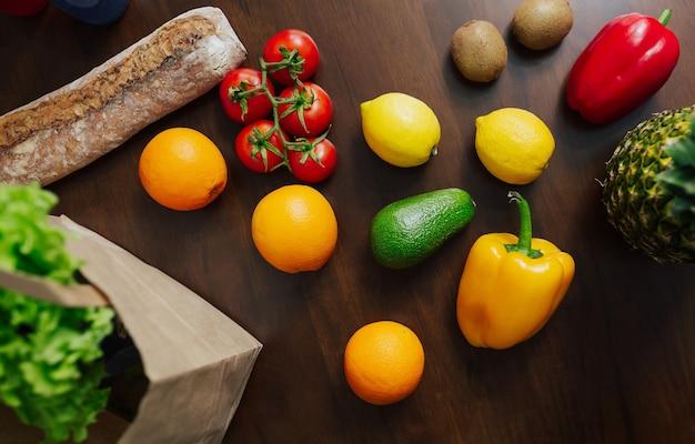 Бумажная хозяйственная сумка, полная овощей и фруктов на столе на кухне.