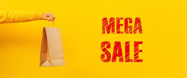 Paper shopping bag in hand over yellow background, mega sale inscription, panoramic image