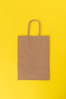 黄色の背景に紙の買い物袋。スペースをコピーします。モックアップ。垂直フレーム