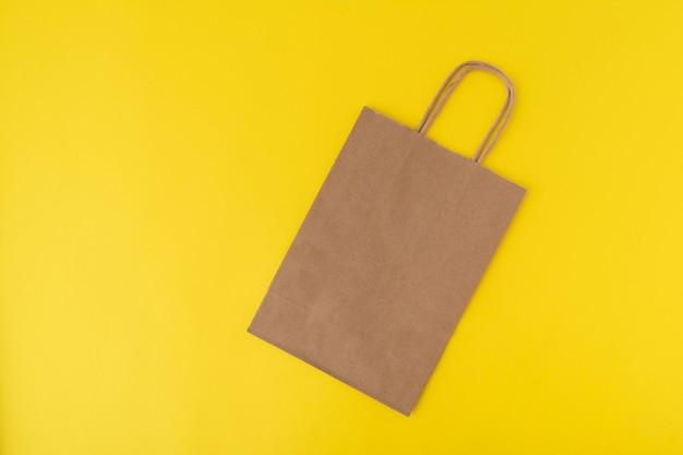 黄色の背景に紙の買い物袋。スペースをコピーします。モックアップ。ゼロウェイスト。