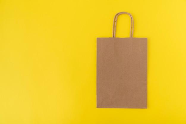 黄色の背景に紙の買い物袋。スペースをコピーします。モックアップ。