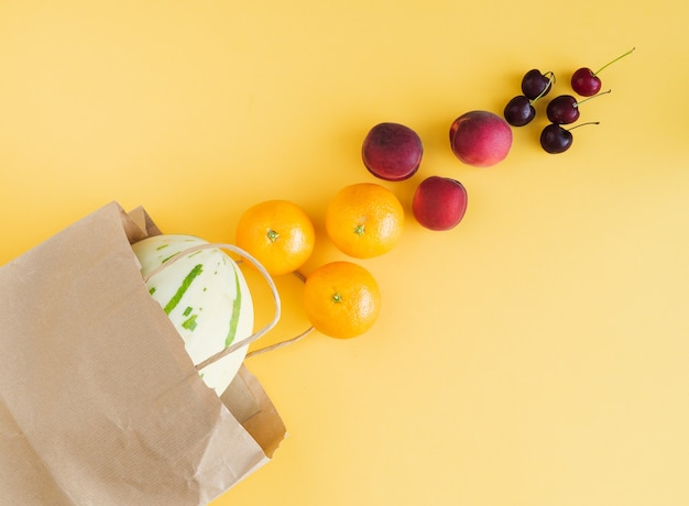 Paper shopping bag with assorted fruit coming out of the bag on yellow background. copy space. top view.