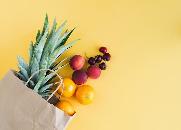 노란색 배경에 가방에서 나오는 다양한 과일이 있는 종이 쇼핑백. 공간을 복사합니다. 평면도.