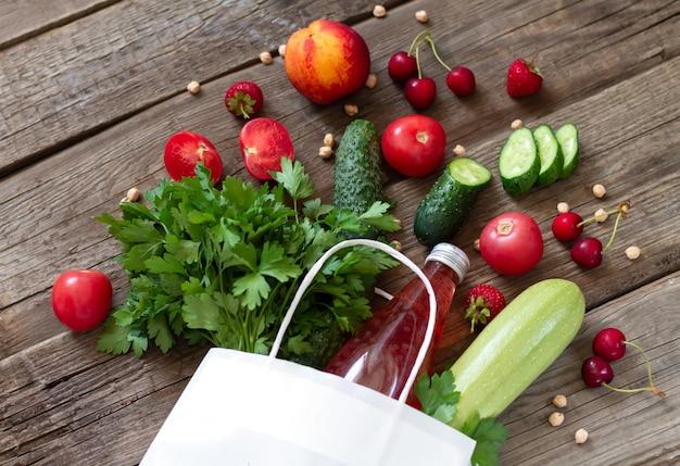 나무 책상에 신선한 채소, 과일, 딸기, 허브, 주스가 담긴 종이 쇼핑백