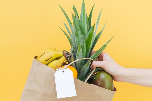 노란색 배경에 여성의 손이 달린 빈 라벨과 과일이 있는 종이 쇼핑백. 모형. 공간을 복사합니다.