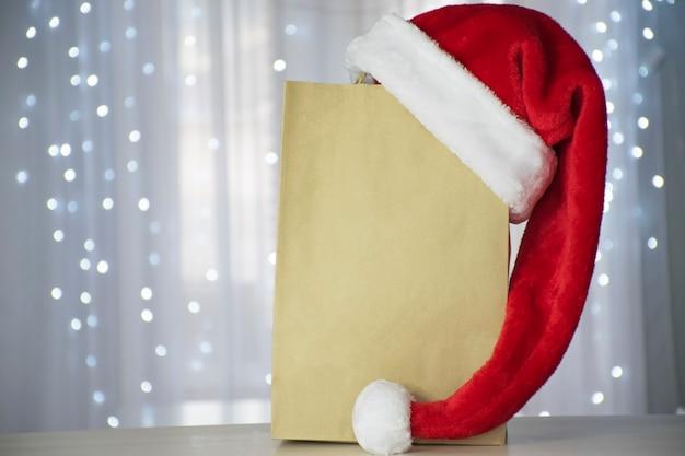 테스트를위한 장소가있는 종이 쇼핑백과 크리스마스 불빛이있는 산타 모자