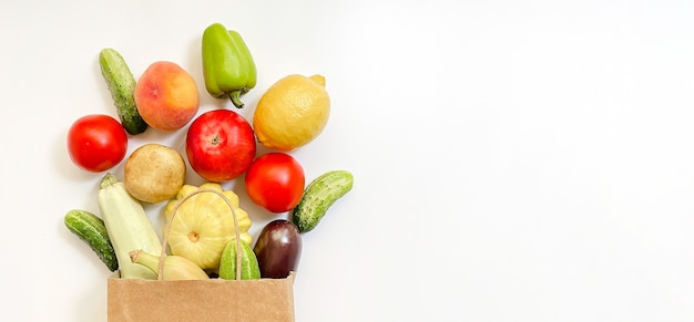 A paper shopping bag with vegetables and fruits, tomato, cucumber, squash, pepper, lemon, eggplant, zucchini, banana, apple, peach on white background.  online shopping concept.