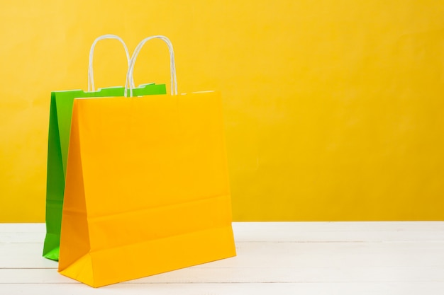 Paper shopping bags on bright yellow background