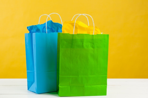 Paper shopping bags on bright yellow