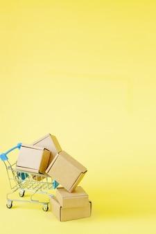 黄色の背景、コンセプトのオンラインショッピングのショッピングカートに紙の買い物袋。