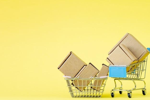 Бумажные хозяйственные сумки в магазинной тележкае на желтой таблице, покупках концепции онлайн.