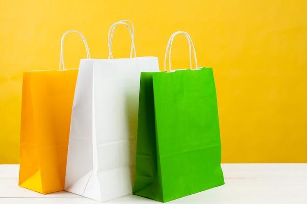 Бумажные хозяйственные сумки на ярко-желтом фоне