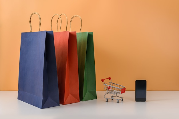 Paper shopping bags and shopping cart or trolley with smartphone on white table and pastel orange wall