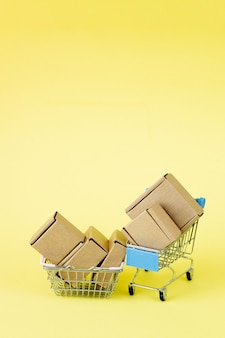 Paper shopping bags in a shopping cart on yellow wall, concept online shopping.