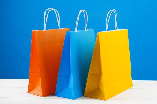 Бумажные хозяйственные сумки с копией пространства на синем фоне