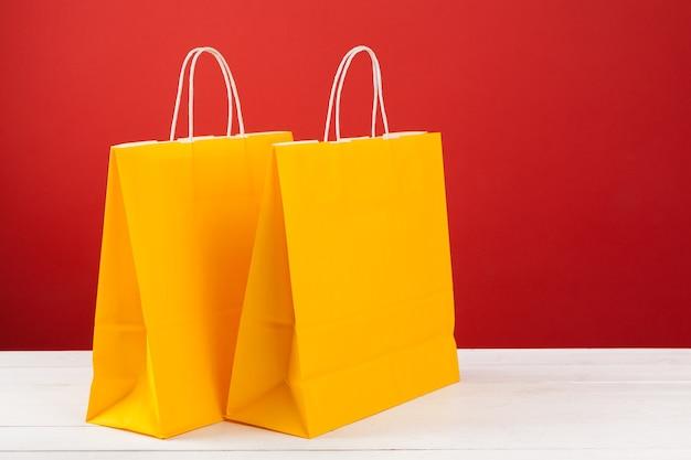 Бумажные хозяйственные сумки с копией пространства на красном фоне