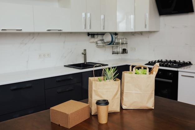 Бумажные хозяйственные сумки с продуктами, кофейной чашкой и картонной коробкой на кухонном столе.