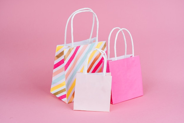 Paper shopping or gift bags on pink background with copy spaсe. concept sales, shopping, black friday.