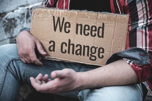 テキスト付きの紙のサイン変更が必要です。男が抱きしめる。経済政策、政治体制環境など、より良い生活のために変化する必要性に抗議する概念生活を変えることは世界を変える。