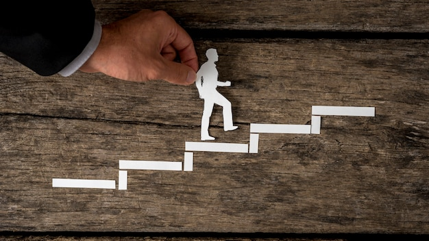 Paper silhouette cutout of a man and a human hand in business suit helping him climb the stairs over rustic wood.
