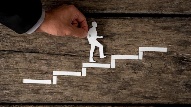 Бумажный вырез силуэта человека и человеческой руки в деловом костюме, помогающей ему подняться по лестнице по деревенскому дереву.