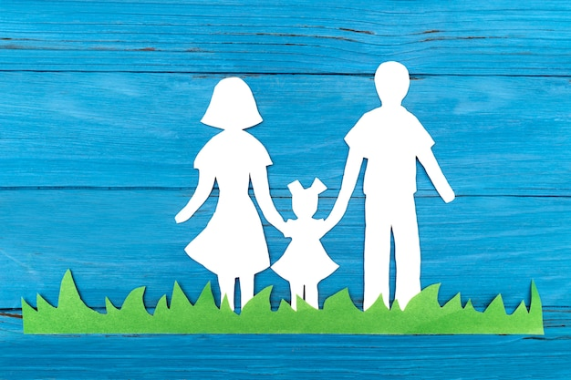 Paper silhouette of a family standing on the green grass
