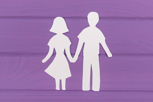 Paper silhouette of man and woman holding hands