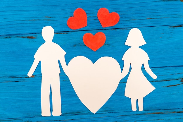 Paper silhouette of man and woman holding heart