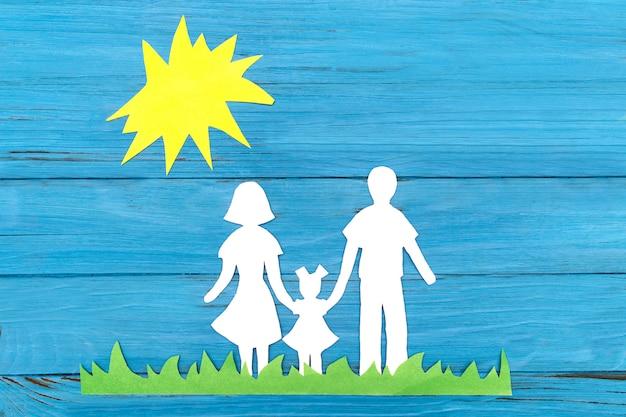 太陽の下で緑の芝生に家族で立っての紙のシルエット
