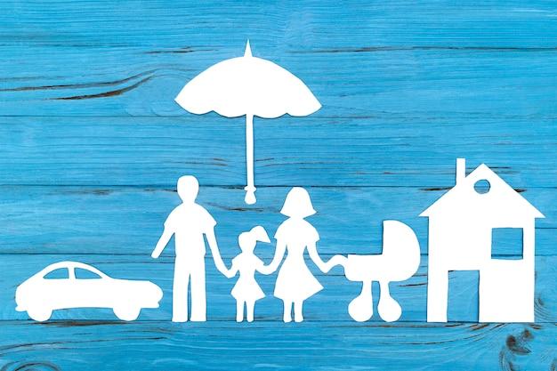 傘の下でベビーカーを持つ家族の紙のシルエット