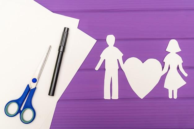 Бумажный силуэт мужчины и женщины, держащей сердце