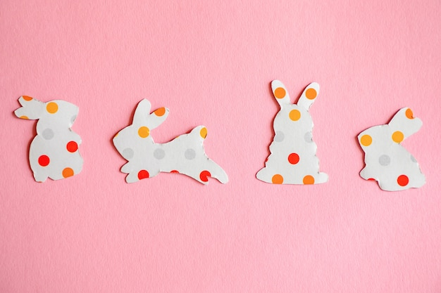 Paper silhouettes of an easter bunnys on pink background