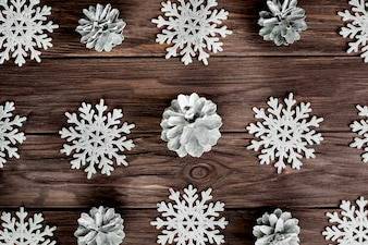 Paper snowflakes and light snags on wooden board