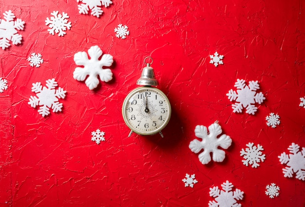 Paper snowflakes and clock on red background