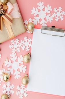Paper snowflakes, folder and golden balls on pink background