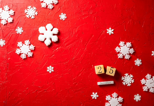 Paper snowflakes and wooden calendar on red background