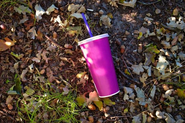地面の森に投げられたプラスチック製の蓋とストローが付いた紙のソフトドリンクカップ、自然界のミルクセーキまたはソーダの紙コップ、テキストの背景用の空白スペース